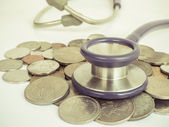 Stethoscope and coins vintage style — Stock Photo