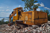 Old excavator on the ruins of an old house. — Stockfoto