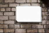 Brick wall texture with empty white plate — Stockfoto