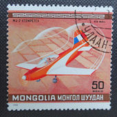 MONGOLIA - CIRCA 1980: A stamp printed in MONGOLIA commemorates World Acrobatic Championship in Oshkosh in Wisconsin and it shows a French sports aircraft Jurca MJ-2 Tempete, circa 1980. — Foto de Stock