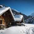 Wooden hut with much snow on roof — Stock Photo