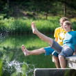 Young couple splashing water at lake sitting on wooden peer — Stock Photo