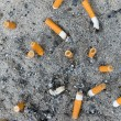 Many ready smoked cigarettes butt stick in sand — Stock Photo