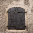 Historical old closed metal window shutter in rough wall — Stock Photo