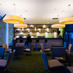 Lonely girl sits alone at modern illuminated hotel bar — Stock Photo