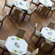 Decorated tables and leather chairsn arranged on wooden floor — ストック写真