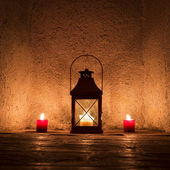 Vintage candlelit in metal lantern standing in stone wall niche — Stock Photo
