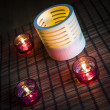 Tea candles in wood and glass standing on reed mat — Stock Photo
