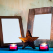 Two wooden picture frames in front of candle light and star — Stock Photo