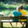 Lovely young couple sitting on seat bench — Stock fotografie
