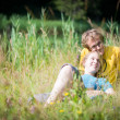 Young lovely couple lying in high grass — Stock Photo