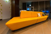 Perspective of huge yellow orange sofa in hotel lobby — Stock Photo