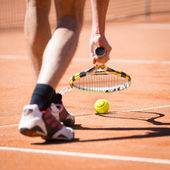 Sportsman catchs up his tennis ball with racket — Stock Photo
