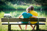 Lovely young couple sitting on seat bench — Stock Photo