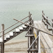 Blocked obsolete wooden catwalk bridge at lake with less water and gravel at coast — Stock Photo