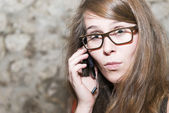 Attractive young woman wearing glasses reacting in surprise to the conversation on a mobile, natural expression with copysapce — Stock Photo