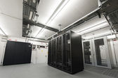 Small air conditioned cooled data server room with black racks and cable trays on ceiling — Stock Photo