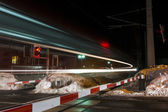 Fast train passing by railroad crossing with closed bar at night — Stock Photo