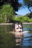 Young boy looks with his eyes out of a lake with nature background — Stock Photo