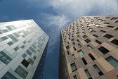 Niedrigen winkel perspektive zwischen zwei modernen kommerziellen wolkenkratzern zum wolkenlos blauen himmel nachschlagen — Stockfoto