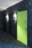 Toilet door made of plexi glass in a swimming pool with dark tiles and flambeus as light — ストック写真
