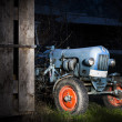 Blue oldtimer farming tractor standing next to a wooden hut at night with red painted tires — Stock Photo #34830529