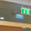Green illuminated exit sign on ceiling — Stock Photo #34830757