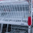 Empty shopping trolley standing outdoor at winter with a red coin lock hanging at a chain — Stock Photo