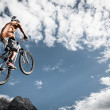 Young boy jumps high with his bike in front of mountains and sky — 图库照片