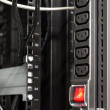 Black power bar in server rack with red main switch button — Stock Photo #34838233