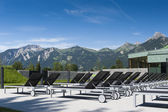Sun loungers of a swim bath with tyrolean mountains in background — Stock Photo