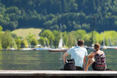 Rear view of a young couple sitting on a lakeshore in the summer sunshine admiring the moored boats and yachts — Stock Photo