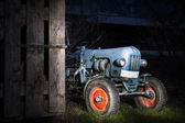 Blue oldtimer farming tractor standing next to a wooden hut at night with red painted tires — Stock Photo