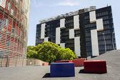Städtische umwelt mit modernen wolkenkratzern und einem zement-gehweg mit rechteckigen blöcken für sitzmöbel — Stockfoto