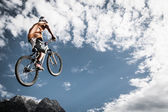 Young boy jumps high with his bike in front of mountains and sky — Stock Photo