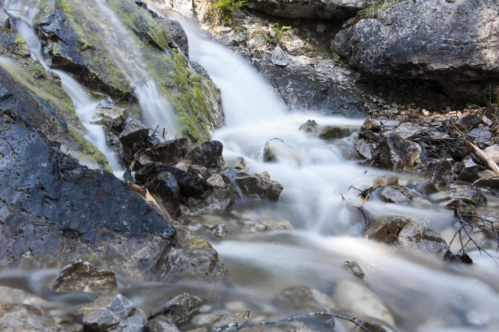 Acqua fredda alp che scorre su pietre grezze a montagne ...