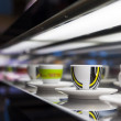 Various cups and saucers with different patterns in a row on a restaurant countertop with selective focus to one cup — Stock Photo