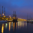 Nightscene with a rigged schooner and tall sailing ships in a peaceful calm harbour with colourful city lights from the waterfront reflected on the water — Stock Photo #34849851