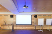 Blue reflections of video projector in wooden conference room — Stock Photo