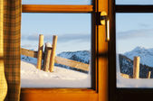 View through window of a hut with very much snow and mountains at a winter day — Stock Photo