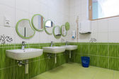 Bathroom with mirrors arranged as caterpillar, washbowls and green grass a tile design in a kindergarten — Stock Photo
