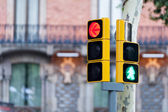 Red traffic light with an arrow halting traffic turning left together with an illuminated little green man. indicating that it is safe for pedestrians to cross on an urban traffic light — Stock Photo