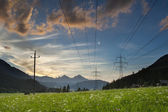 Power lines and electric pylons crossing a lush mountain meadow as the sun sets on glowing clouds — Stock Photo