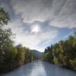 River between trees at autumn with cloudy sky and sun beam — Lizenzfreies Foto