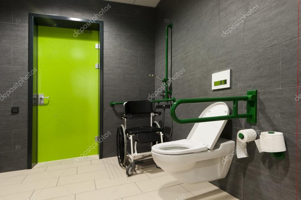 A toilet for disabled people with green bars wheelchair - Toilet for handicapped person ...