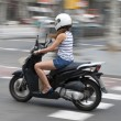 Woman riding a motorcycle down an urban street in shorts and summer top with motion blur — Stock Photo