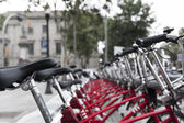 View straight down a row of identical red bicycles parked in an urban environment probably up for hire to tourists — ストック写真