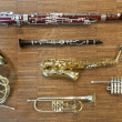 Stock Photo: Several wind instruments laying on wooden floor. trumpet, horn, saxophone, clarinet, flute, bassoon, curtal