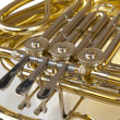 Stock Photo: Detail of brass and silver horn or bugle with valves lying on a white background
