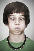 Portrait of cross-eyed young teenager boy with necklace and green pullover — Stock Photo